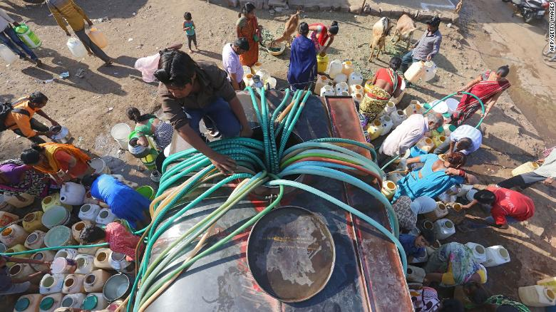 Indian slum dwellers collect potable water from a municipal water tanker in Durga Nagar.