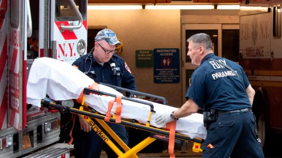 """FDNY paramedics place an empty collapsible wheeled stretcher into an ambulance after delivering a patient into the emergency room at NewYork-Presbyterian Lower Manhattan Hospital, Wednesday, March 18, 2020, in New York. """"Do not go to the emergency room unless it is a true, immediate and urgent emergency,"""" said Mayor Bill de Blasio, who pleaded Tuesday with people who suspect they have coronavirus symptoms to stay home and see if they improve in a few days before even calling a doctor. For most people, the new coronavirus causes only mild or moderate symptoms. For some it can cause more severe illness. (AP Photo/Mary Altaffer)"""