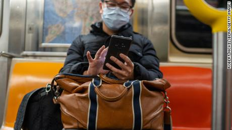 A passenger wearing a surgical mask uses his iPhone while riding an uptown subway in New York City on March 18, 2020. New York City subways are nearly empty with most businesses closed and people voluntarily sheltering due to the spreading of the Coronavirus.