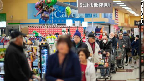 Shoppers wait in the checkout line at a Stop & Shop supermarket on Thursday, March 19, 2020, in North Providence, Rhode Island.