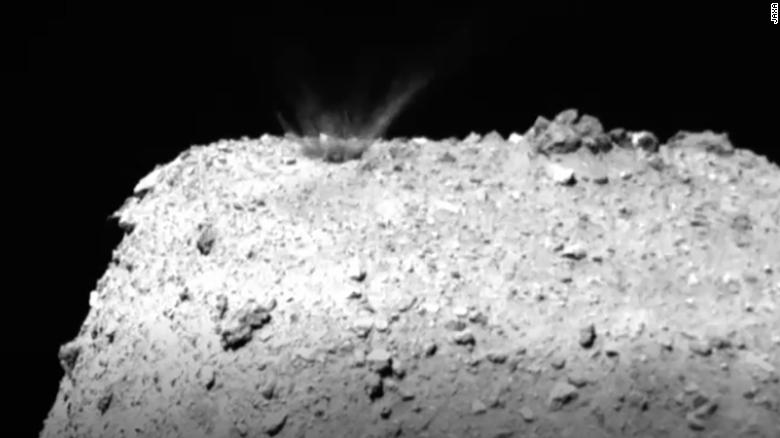 This still from a video created by images captured by Hayabusa 2 shows material being ejected and falling back onto the asteroid after impact.
