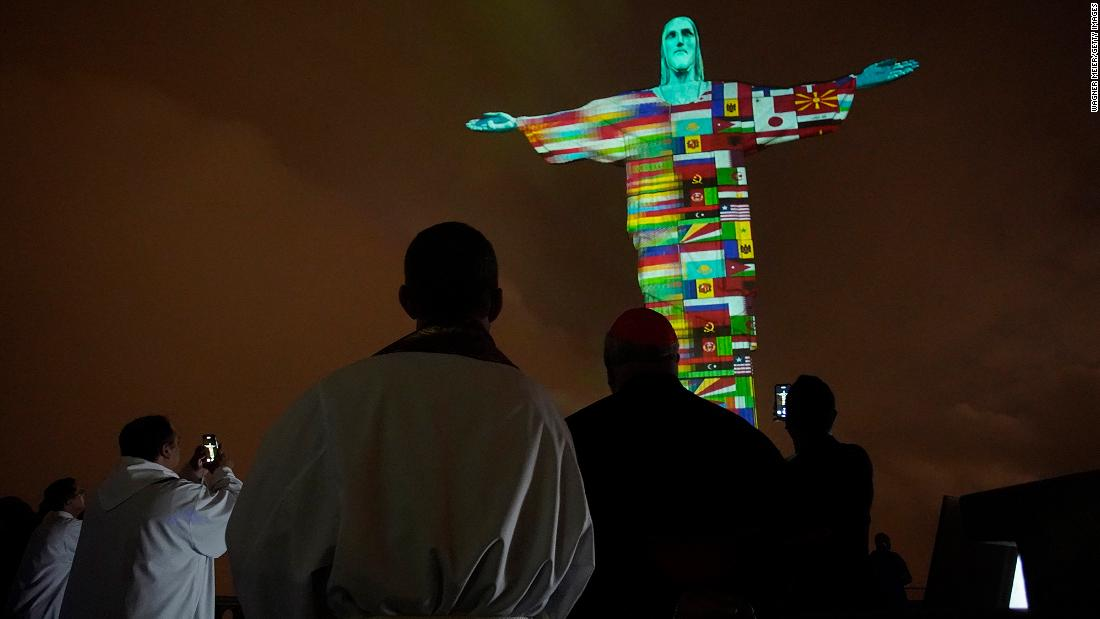 "A Mass in Rio de Janeiro honors coronavirus victims around the world on March 18. Brazil's Christ the Redeemer statue <a href=""https://www.cnn.com/travel/article/coronavirus-rio-christ-the-redeemer-trnd/index.html"" target=""_blank"">was lit up with flags and messages of hope</a> in solidarity with countries affected by the pandemic."
