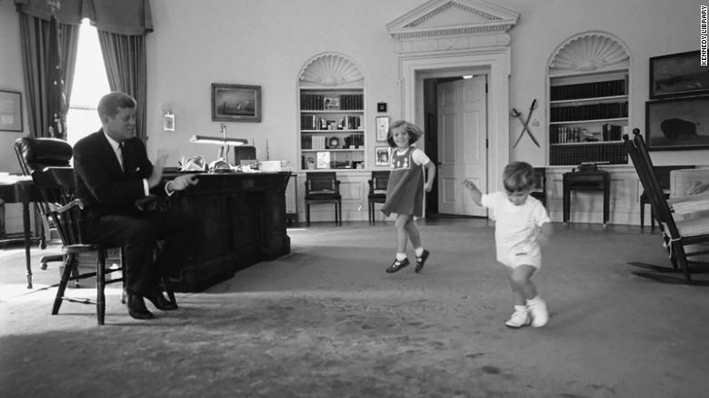 ජෝන් එෆ් කෙනඩි අත්පුඩි ගසද්දී ඔහුගේ දරුවන් වන කැරොලයින් කෙනඩි සහ ජෝන් එෆ් කෙනඩි කනිෂ් ,, 1962 ඔක්තෝබර් 10 වන දින ඕවල් කාර්යාලයේ නටති. (අනුග්රහය කෙනඩි පුස්තකාලය)