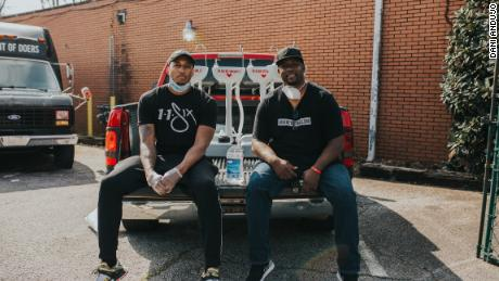 Hip hop artist Lecrae (left) and Love Beyond Walls founder Terence Lester (right) distribute portable wash stations around Atlanta.