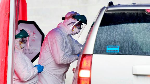 Clinical care providers take swabs for coronavirus on a patient during drive-thru testing by the Fayette County Health Department in Oak Hill, West Virginia, on Thursday, March 19, 2020.