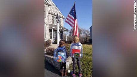 Two sisters outside their Pennsylvania home recite the Pledge of Allegiance.