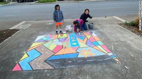Daphne Sashin, her 8-year-old son Jack and 5-year-old daughter Lucy work on their sidewalk drawing as part of the community activity Sashin planned in their Mountain View, California, neighborhood.