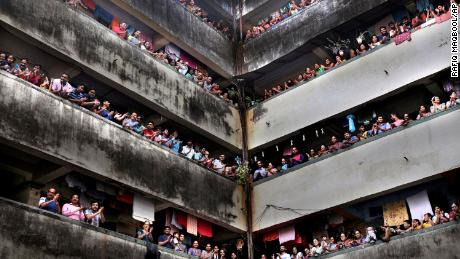 People clap from balconies at a chawl in Mumbai on Sunday.