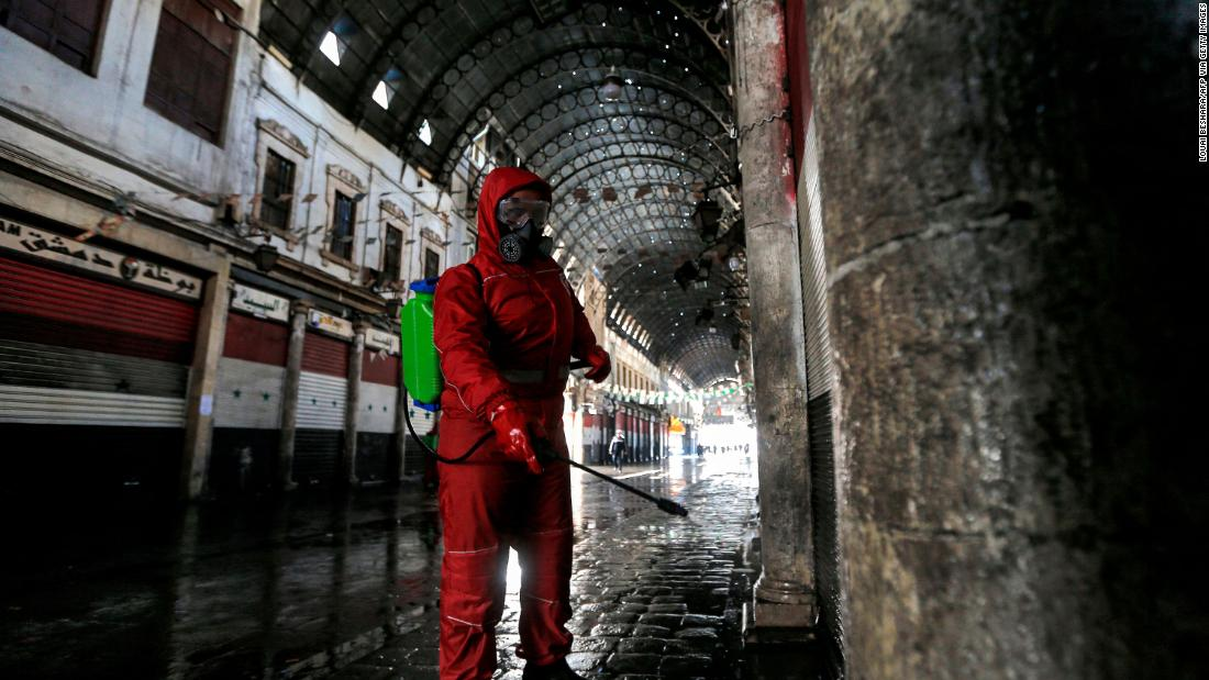 A Syrian Red Crescent member sprays disinfectant along an alley of the historic Hamidiyah market in Damascus, Syria.