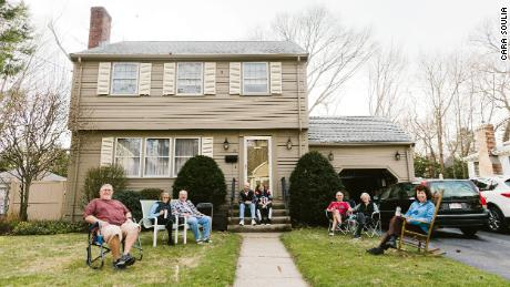 A group of people photographed on one of their front lawns. The group, who was enjoying a warm Friday afternoon, maintained six feet of distance between each other.
