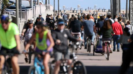 People ride their bikes on March 21, 2020, in Huntington Beach, California.