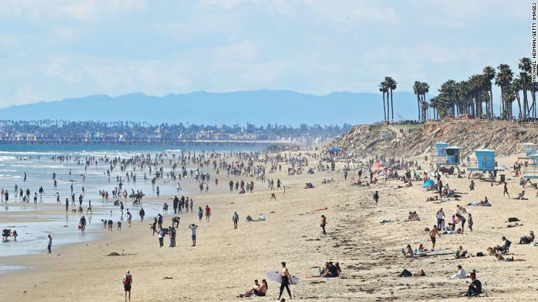 People are seen on the beach on March 21, 2020 in Huntington Beach, California. California Governor Gavin Newsom issued a statewide 'stay at home' order for California's 40 million residents except for 'necessary activities' in the hopes of slowing the spread of coronavirus (COVID-19).