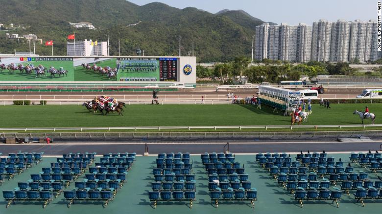 Horses gallop past the empty public stands at Sha Tin Racecourse.