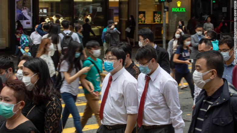 Office workers and pedestrians wearing protective masks walk along Queen's Road Central in the Central district of Hong Kong on Friday, March 20, 2020.