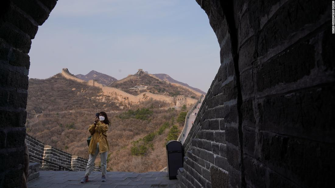 "A tourist wears a face mask while visiting the Badaling section of the Great Wall of China on March 24. The section <a href=""https://www.cnn.com/travel/article/badaling-great-wall-china-reopens-intl-hnk/index.html"" target=""_blank"">reopened</a> to visitors after being closed for two months."