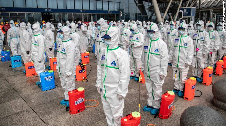 Staff members line up as they prepare to disinfect Wuhan Railway Station on Tuesday, March 24.