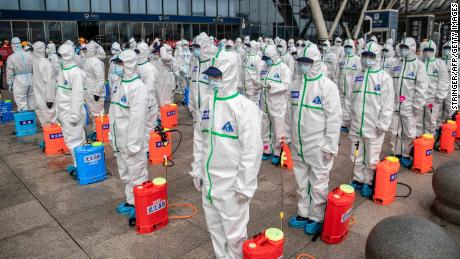 Staff members line up at attention as they prepare to spray disinfectant at Wuhan Railway Station in Wuhan in China's central Hubei province on March 24, 2020. - China announced on March 24 that a lockdown would be lifted on more than 50 million people in central Hubei province where the COVID-19 coronavirus first emerged late last year. (Photo by STR / AFP) / China OUT (Photo by STR/AFP via Getty Images)