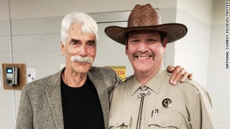 "Tim, right, has become an internet favorite after he was put in charge of a museum's social media accounts. He is photographed here with actor Sam Elliot and Elliot's ""quality mustache."""