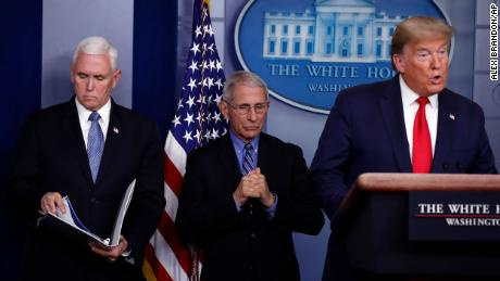 Vice President Mike Pence and Dr. Anthony Fauci, director of the National Institute of Allergy and Infectious Diseases, listen as President Donald Trump speaks about the coronavirus in the James Brady Briefing Room, Tuesday, March 24, 2020, in Washington. (AP Photo/Alex Brandon)