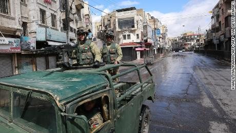 Soldiers patrol atop a military vehicle on deserted street in Amman.