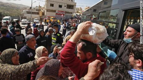 People queue to buy subsidised bread from a municipal bus in the Marka suburb of Amman on Tuesday.