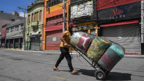 A street vendor walks along an empty street in downtown Sao Paulo, Brazil, on Tuesday.