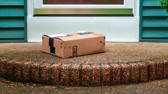 A package is delivered and placed on a wet stoop in the rain in the front of a house exposed to the elements and theft by a delevery service.