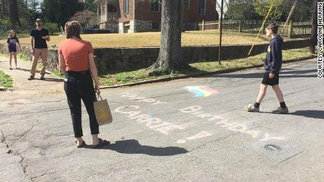 Friends draw in chalk on the street to wish Carrie Crespino a happy birthday.