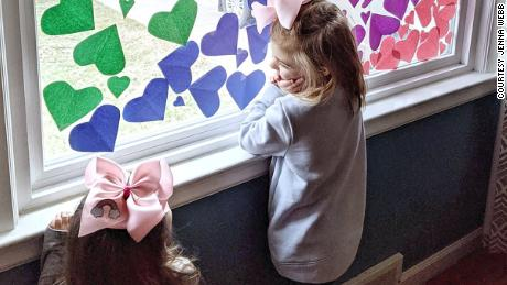 "Josephine, 5, and Nora, 2, look out their rainbow heart-filled window in Michigan. Their mother, Jenna Webb, said she wanted to ""bring love and joy to essential workers"" in their neighborhood."