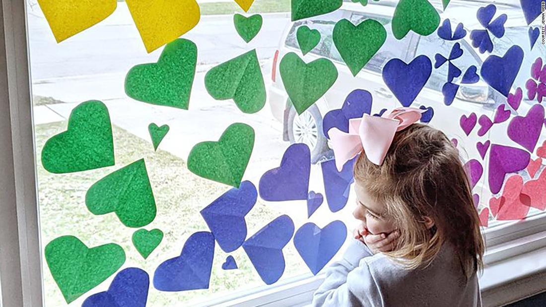 Οι άνθρωποι διακοσμούν τα παράθυρα με τις καρδιές και τα μηνύματα της ελπίδας τώρα