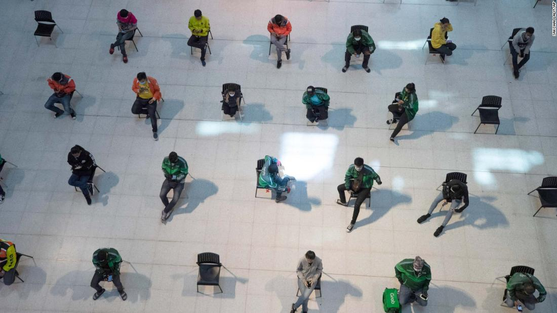 People practice social distancing as they wait for takeout food at a shopping mall in Bangkok, Thailand, on March 24.