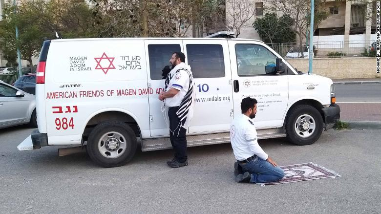 Jewish paramedic Avraham Mintz faces Jerusalem, his prayer shawl hanging off his shoulders. Muslim paramedic Zoher Abu Jama kneels facing Mecca, his prayer rug unfurled before him.