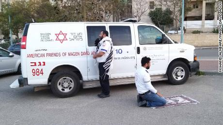 Jewish paramedic Avraham Mintz faces Jerusalem, his prayer shawl hanging off his shoulders. Muslim paramedic Zoher Abu Jama kneels facing Mecca, his prayer rug unfurled before him.