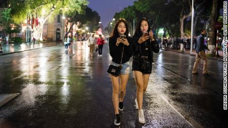 Two young women walking alonga street with their smartphones in Hanoi, Vietnam, 30 October 2016. PHOTO: GREGOR FISCHER/dpa | usage worldwide   (Photo by Gregor Fischer/picture alliance via Getty Images)