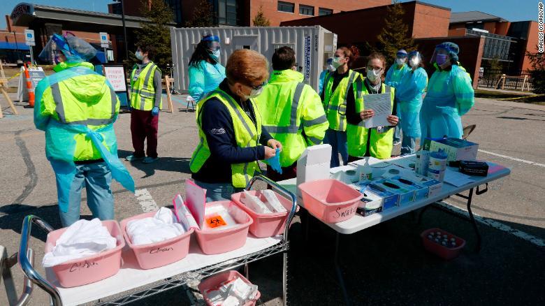 医护人员周三在密歇根州亨利·福特西布卢姆菲尔德医院的冠状病毒通过测试现场准备了补给品。
