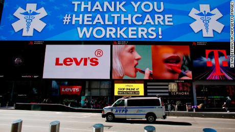 A police van is seen under a sign thanking healthcare workers in Times Square on March 22, 2020 in New York City.