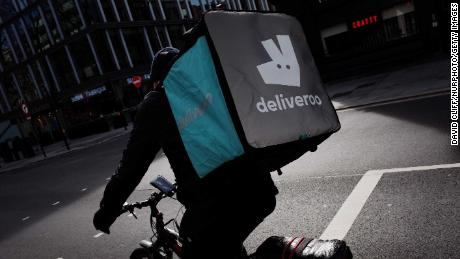 A Deliveroo courier cyclist waits at traffic lights on a near-deserted Tottenham Court Road in London, England, on March 21, 2020. Much of central London was virtually empty today, a day after British Prime Minister Boris Johnson ordered the closure of all pubs, bars, cafes and restaurants around the country. The move represents a toughening of measures to enforce the 'social distancing' that is being urged on citizens to reduce the growth of covid-19 coronavirus infections. Nightclubs, theatres, cinemas, gyms and leisure centres were also ordered closed. Some shops in the centre of capital remained open today, albeit mostly deserted of customers; many retailers however have temporarily closed their doors until the crisis abates. (Photo by David Cliff/NurPhoto via Getty Images)