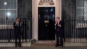 Boris Johnson, right, taking part in a national applause with his chancellor, Rishi Sunak.