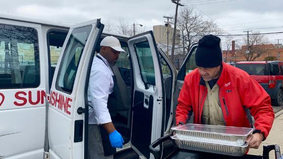 Hardy helps volunteer load meals into a van.