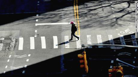 A person crosses the street on March 27, 2020 in New York City. - The US now has more COVID-19 infections than any other country, and a record number of newly unemployed people, as the coronavirus crisis deepens around the world. (Photo by Angela Weiss/AFP/Getty Images)