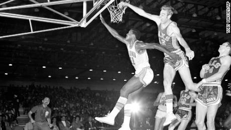 In this November 28, 1968, file photo, Miami Floridians' Les Hunter (41) is fouled by Oakland Oaks' Jim Eakins (42) while scoring a basket during an ABA basketball game in Miami.