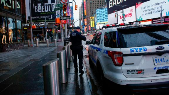 A NYPD officer patrols Times Square as rain falls on March 28, 2020 in New York City. - US President Donald Trump said on March 28, 2020 that he's considering a short-term quarantine of New York state, New Jersey, and parts of Connecticut. (Photo by Kena Betancur / AFP) (Photo by KENA BETANCUR/AFP via Getty Images)