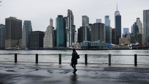 People walk in Brooklyn while lower Manhattan looms in the background on March 28, 2020 in New York City, NY. Across the country schools, businesses and places of work have either been shut down or are restricting hours of operation as health officials try to slow the spread of COVID-19.