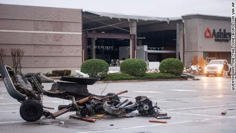 The damaged remains of a vehicle lie in a parking lot outside a damaged Ashley HomeStore after the tornado Saturday in Jonesboro.