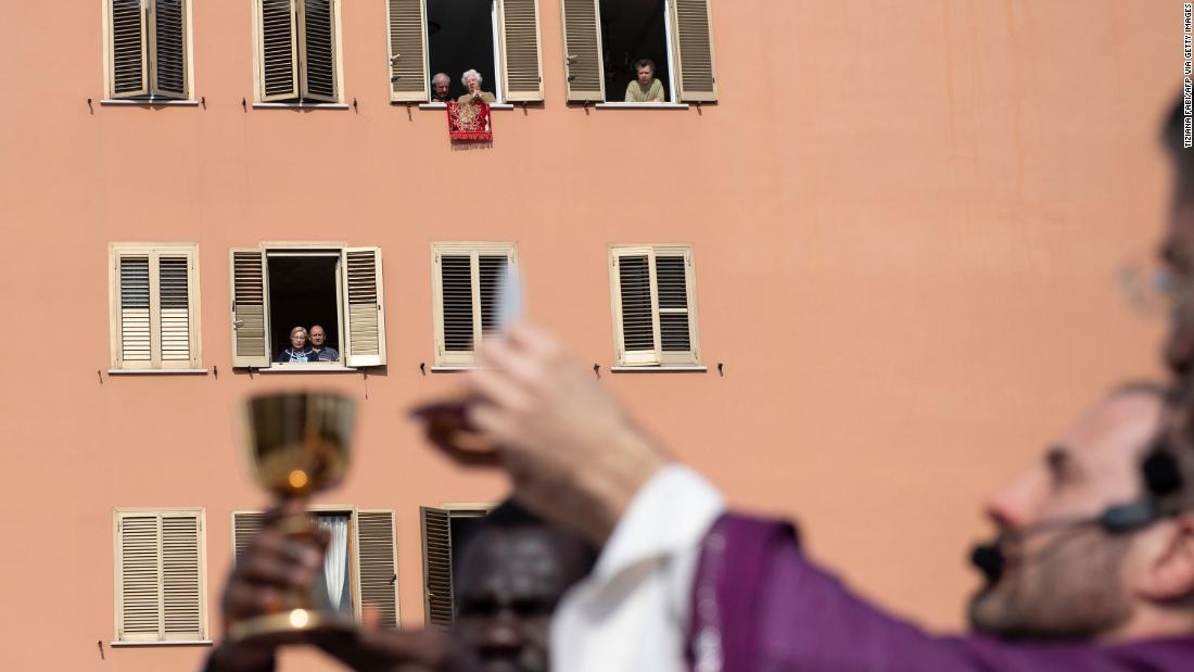 People listen from their homes as priests conduct Sunday mass from a church roof in Rome on March 29, 2020.