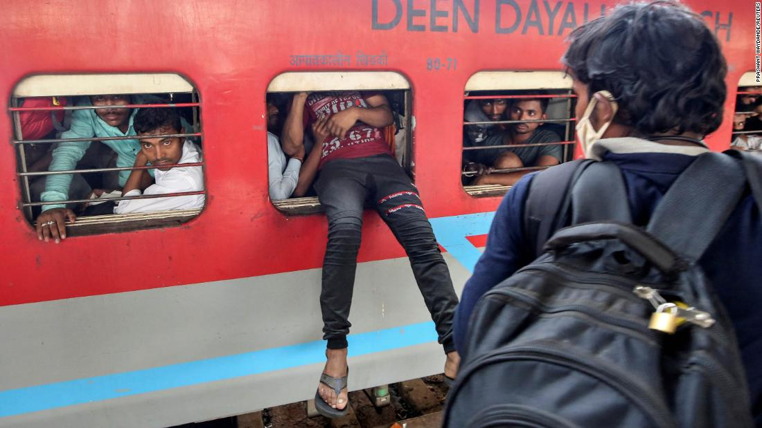 A migrant worker attempts to board an overcrowded train in Mumbai.