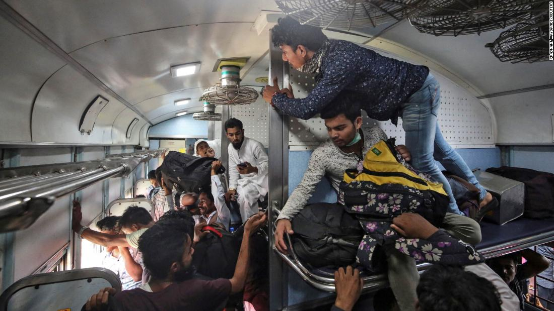 Migrant workers and their families board an overcrowded passenger train in Mumbai on March 21. Many workers had already left India's big cities before this weekend.