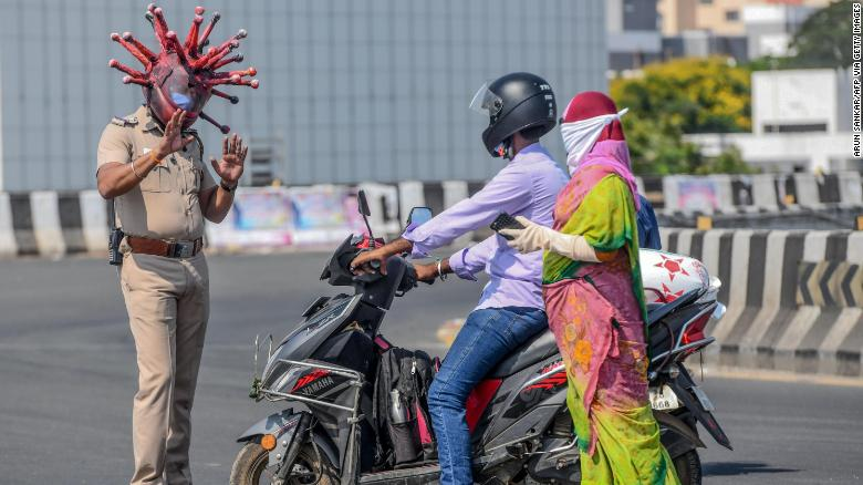 Police inspector Rajesh Babu in a coronavirus-themed helmet, talking to commuters in Chennai, India, on March 28.