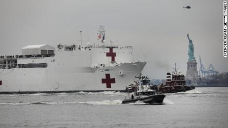 NEW YORK, NY - MARCH 30: The USNS Comfort hospital ship travels up the Hudson River as it heads to Pier 90 on March 30, 2020 seen from Battery Park in New York City. The Comfort, a floating hospital in the form of a Navy ship, is equipped to take in patients within 24 hours but will not be treating people with COVID-19. The ship's 1,000 beds and 12 operation rooms will help ease the pressure on New York hospitals, many of which are now overwhelmed with COVID-19 patients.  (Photo by Spencer Platt/Getty Images)