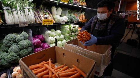 A worker, wearing a protective mask against the coronavirus, stocks produce at Gus's Community Market in San Francisco.